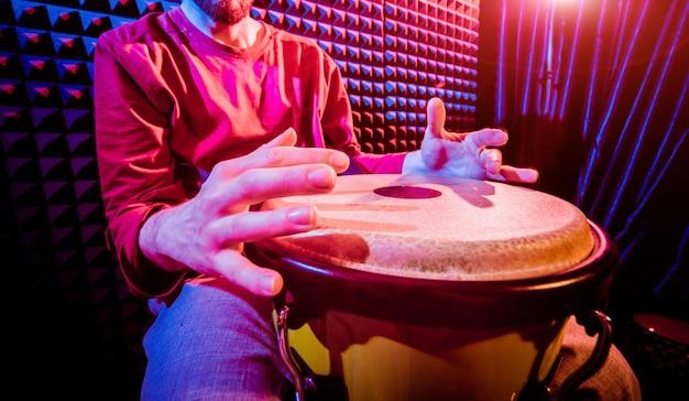 Jonge mens het spelen op djembe in geluidsopnamestudio.