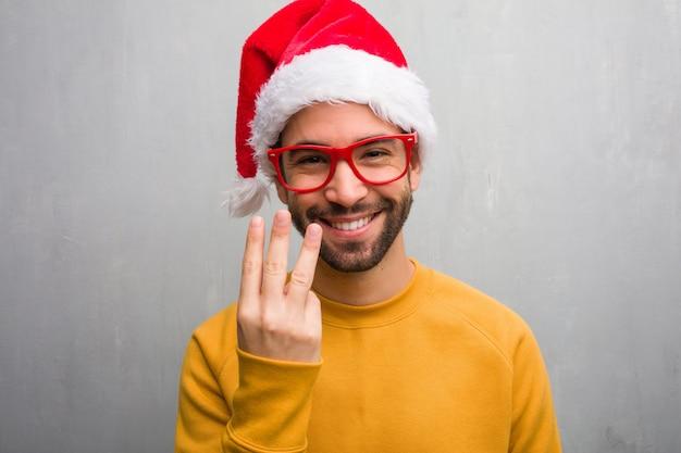 Jonge mens het vieren de holdingsgiften die van de kerstmisdag nummer drie tonen