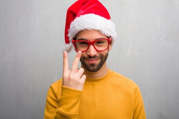 Jonge mens het vieren de holdingsgiften die van de kerstmisdag nummer twee tonen