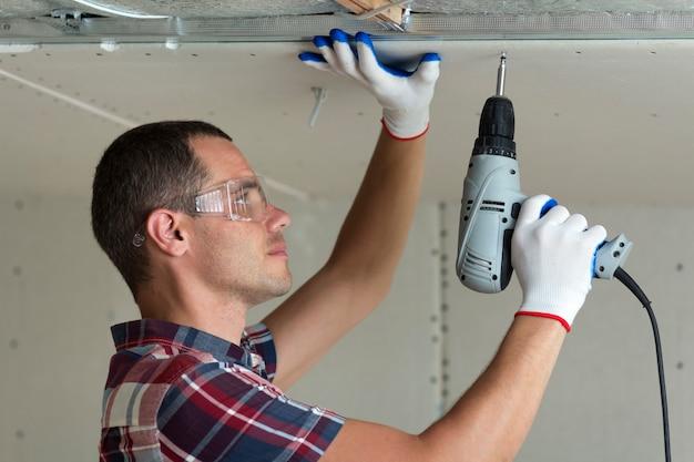 Jonge mens in beschermende brillen die gipsplaten opgehangen plafond bevestigen.