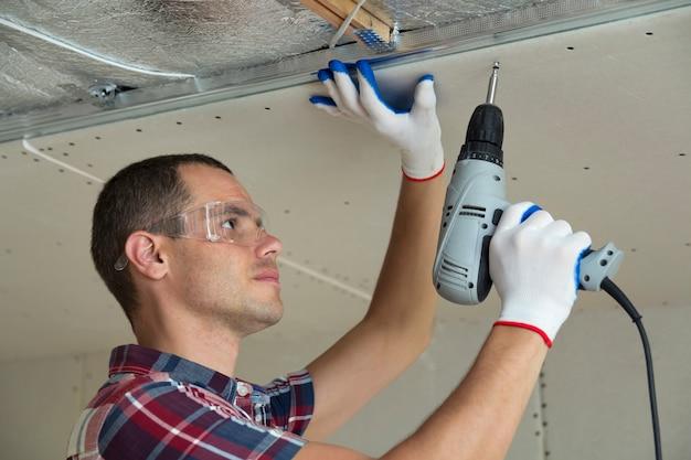 Jonge mens in beschermende brillen die gipsplaten opgehangen plafond bevestigen