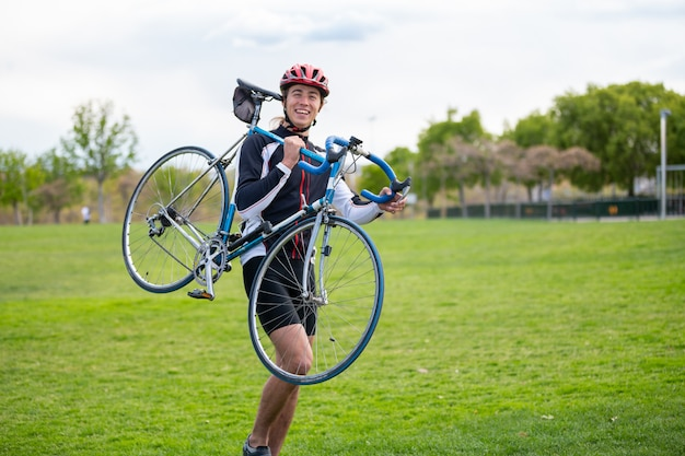Jonge mens in helm en sportkleding die en fiets op schouder glimlachen dragen terwijl het lopen op groen gazon in park