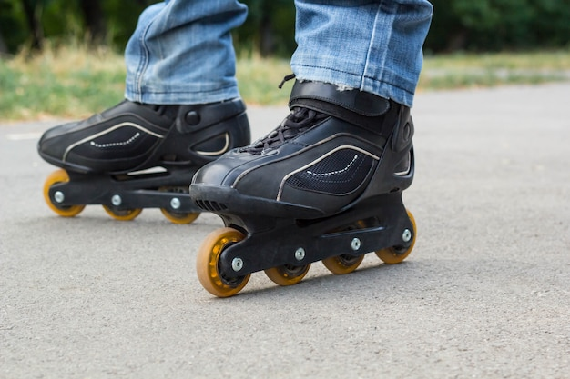 Jonge mens in jeans die rolschaatsen in de stad berijden. close-up benen