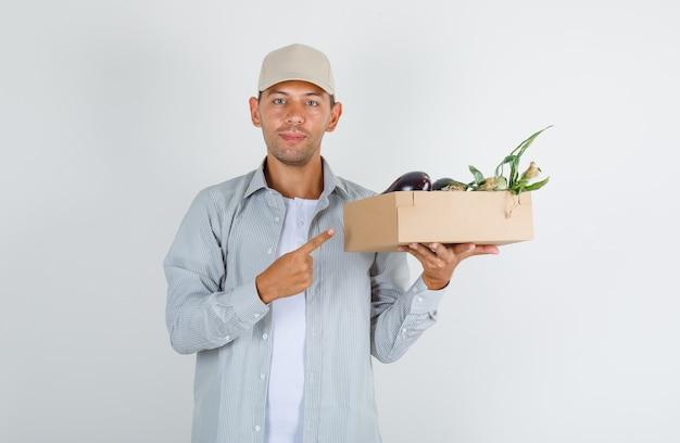 Jonge mens in overhemd met glb die groentedoos met vinger, vooraanzicht tonen.