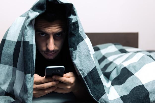 Jonge mens in pyjama's die een cellphone gebruiken terwijl het liggen in bed.