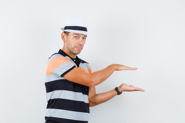 Jonge mens in t-shirt en hoed die klein grootteteken tonen