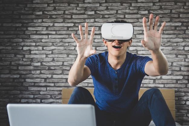 Jonge mens in virtuele werkelijkheidshoofdtelefoon of 3d glazen die videospelletje spelen