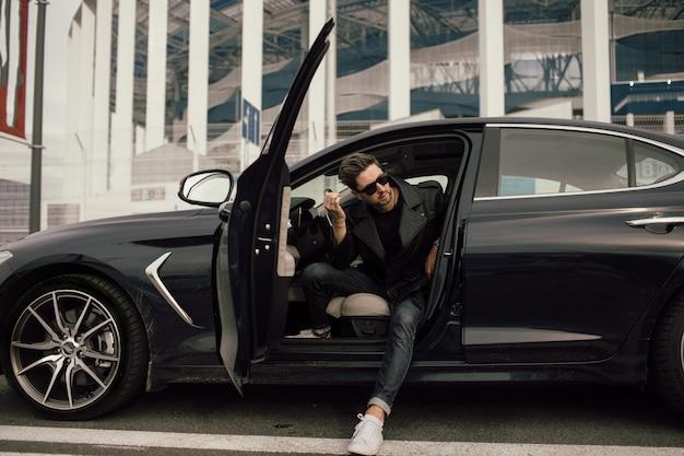Jonge mens in zonnebril die van auto in stad weggaan