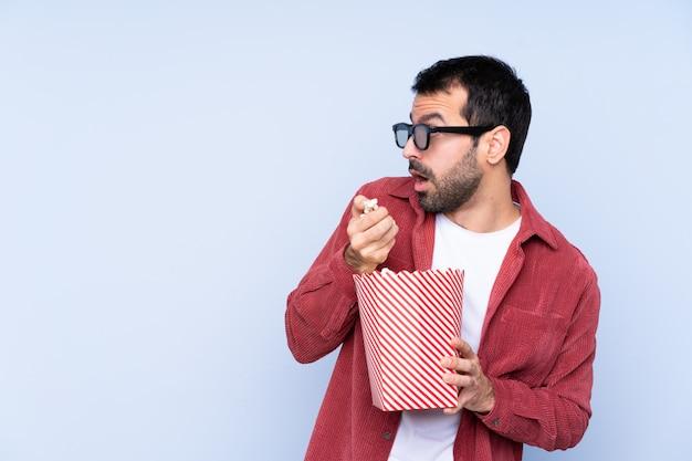 Jonge mens met 3d glazen en het houden van een grote emmer popcorns terwijl het kijken kant