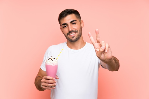 Jonge mens met aardbeimilkshake die en overwinningsteken glimlachen tonen