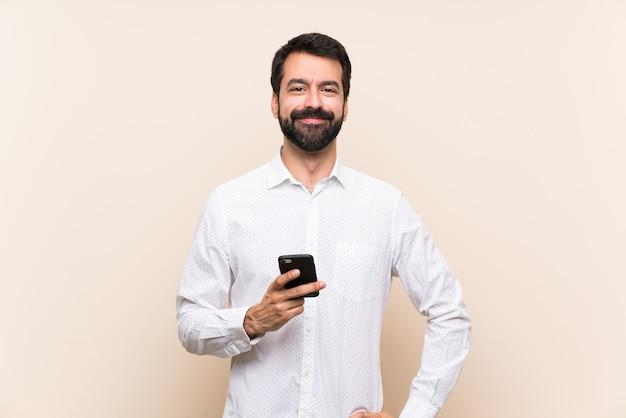 Jonge mens met baard die het mobiele stellen met wapens houden bij heup en het glimlachen