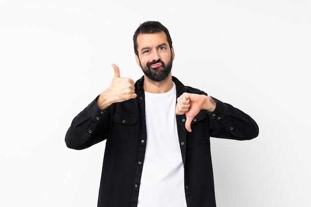 Jonge mens met baard over geïsoleerd wit die goed-slecht teken maken. onbeslist tussen ja of niet