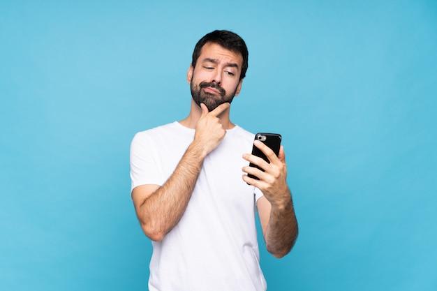 Jonge mens met baard over geïsoleerde blauwe muur die en een bericht denkt verzendt