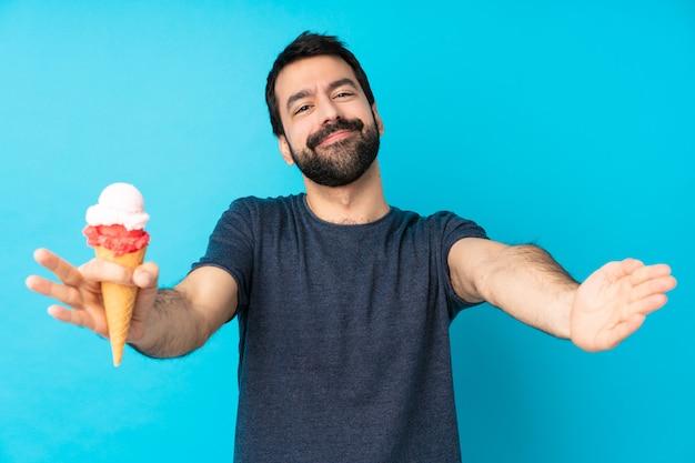 Jonge mens met een cornetroomijs over geïsoleerde blauwe muur die en met hand voorstelt uitnodigt te komen