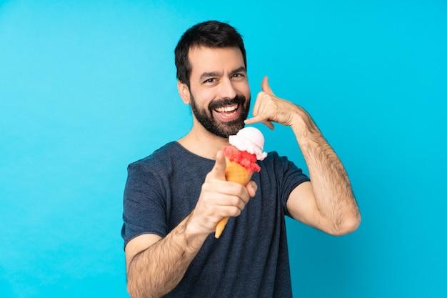 Jonge mens met een cornetroomijs over geïsoleerde blauwe muur die telefoongebaar maken en voorzijde richten