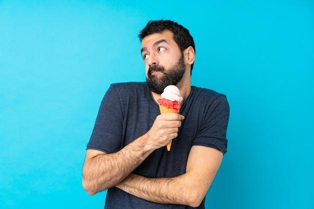 Jonge mens met een cornetroomijs over geïsoleerde blauwe muur die twijfelsgebaar maken terwijl het opheffen van de schouders Premium Foto