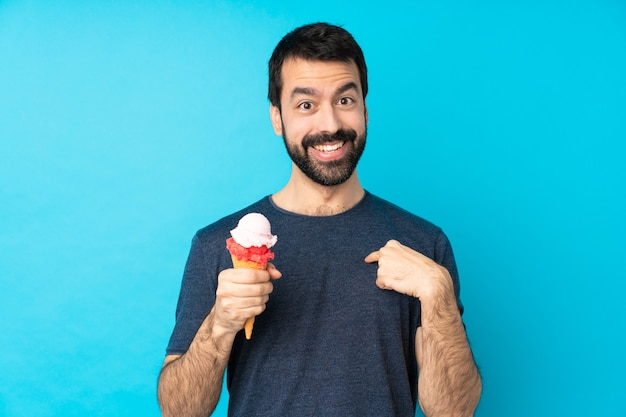 Jonge mens met een cornetroomijs over geïsoleerde blauwe muur met verrassingsgelaatsuitdrukking