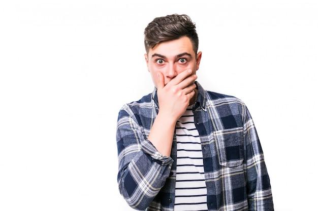 Jonge mens met geschokte gelaatsuitdrukking die over witte muur wordt geïsoleerd