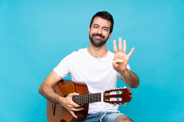 Jonge mens met gitaar over geïsoleerde blauwe gelukkig en tellend vier met vingers