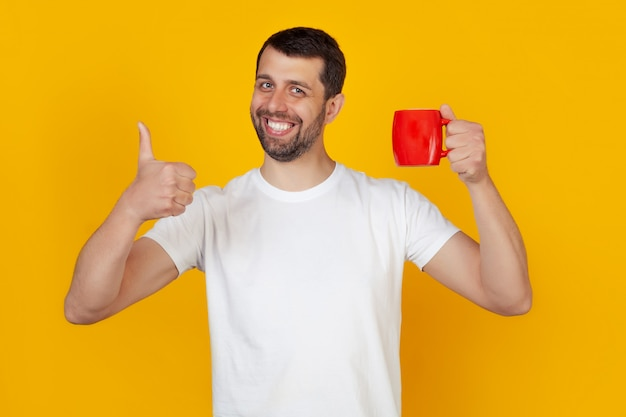 Jonge mens met in hand de mok van de ochtendkoffie die gelukkige duim op gebaar tonen