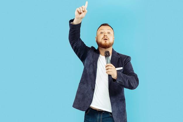Jonge mens met microfoon op blauwe studio, leidend concept