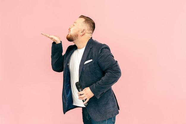 Jonge mens met microfoon op roze, leidend met microfoon bij studioconcept.