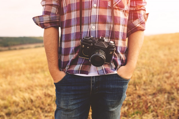 Jonge mens met retro openluchthipsterlevensstijl van de fotocamera