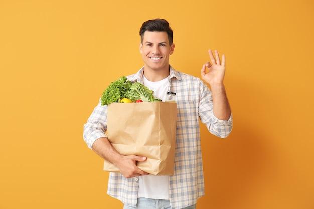 Jonge mens met voedsel in zak die ok gebaar op kleur toont