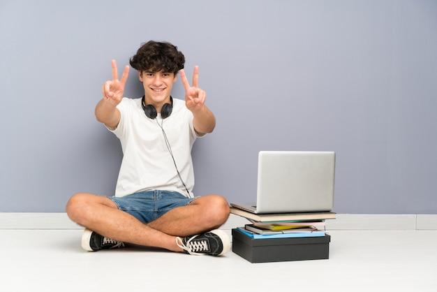 Jonge mens met zijn laptop zitting één de vloer die en overwinningsteken glimlachen tonen