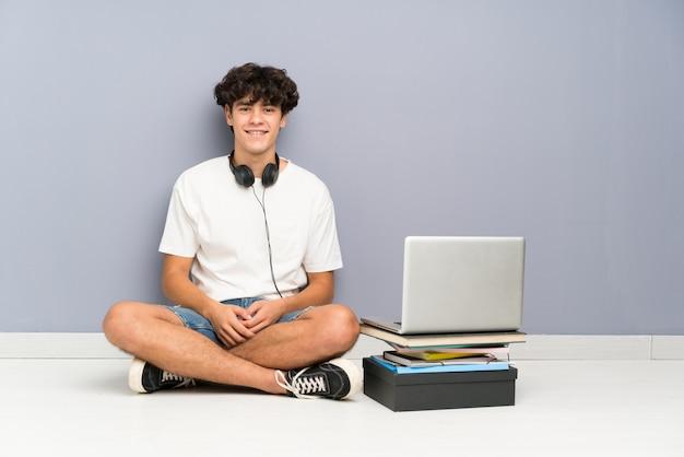Jonge mens met zijn laptop zitting één vloer het lachen