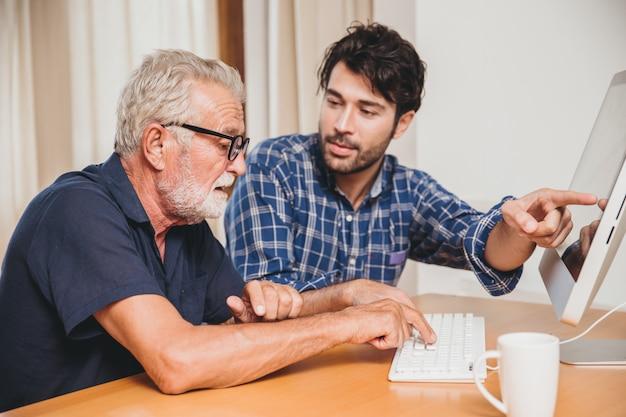 Jonge mens of zoon die zijn grootvader bejaarde papa onderwijzen die aan computer thuis leren gebruiken.
