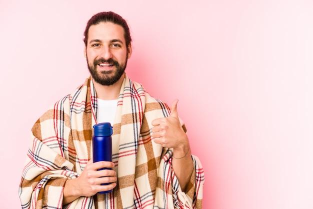 Jonge mens op een het kamperen dag die een thermosfles houden die en duim glimlachen opheffen