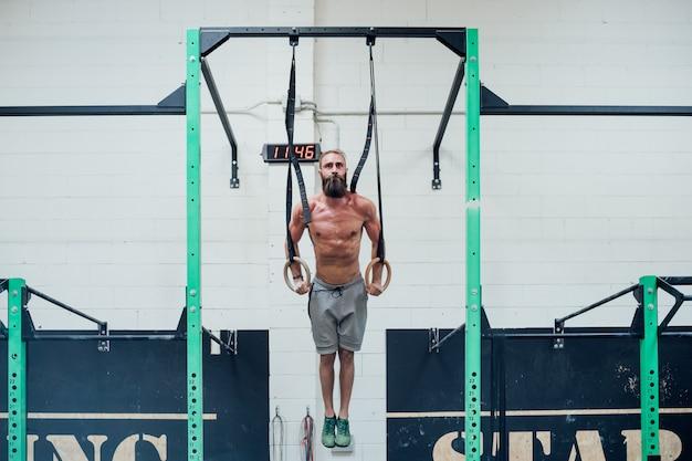 Jonge mens opleiding met ringen binnen dwars geschikte gymnastiek