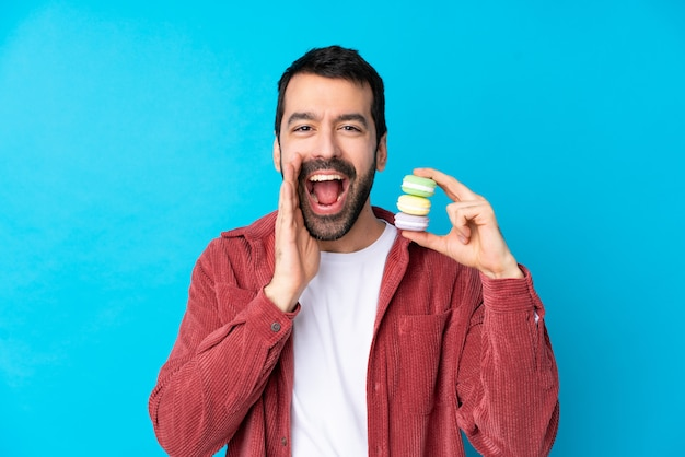 Jonge mens over geïsoleerde blauwe muur die kleurrijke franse macarons en het schreeuwen houdt