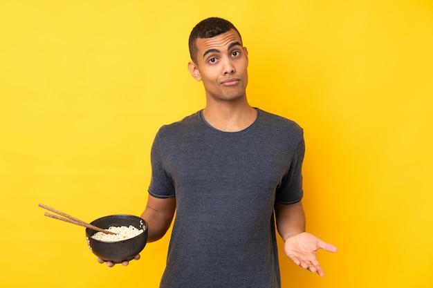 Jonge mens over geïsoleerde gele muur die twijfelsgebaar maken terwijl het opheffen van de schouders terwijl het houden van een kom van noedels met eetstokjes