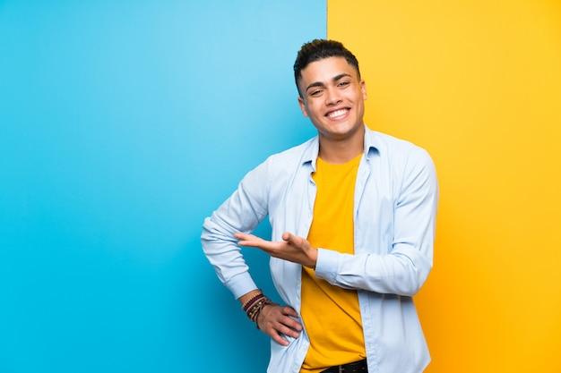 Jonge mens over geïsoleerde kleurrijke achtergrond die handen uitbreiden aan de kant voor het uitnodigen om te komen