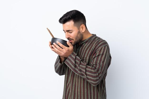 Jonge mens over geïsoleerde muur die een kom van noedels met eetstokjes houdt en het eet