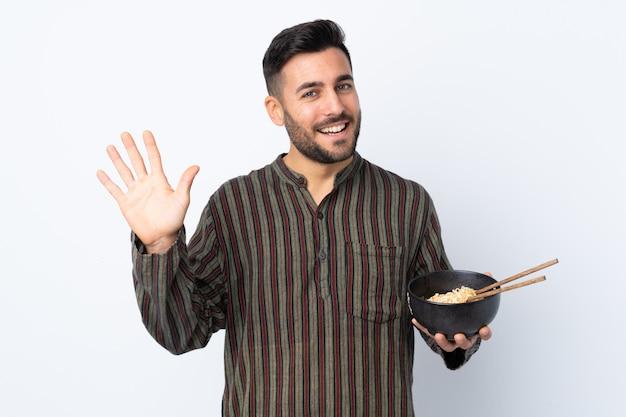 Jonge mens over geïsoleerde muur die met hand met gelukkige uitdrukking groeten terwijl het houden van een kom van noedels met eetstokjes