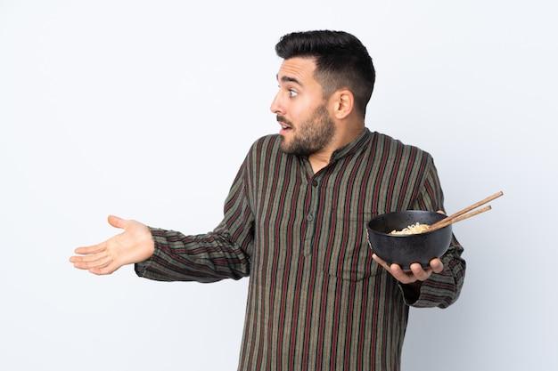 Jonge mens over geïsoleerde muur met verrassingsgelaatsuitdrukking terwijl het houden van een kom van noedels met eetstokjes