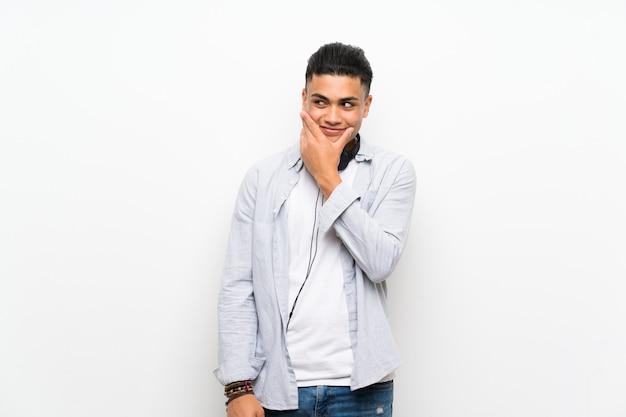 Jonge mens over geïsoleerde witte muur met oortelefoons die een idee denken