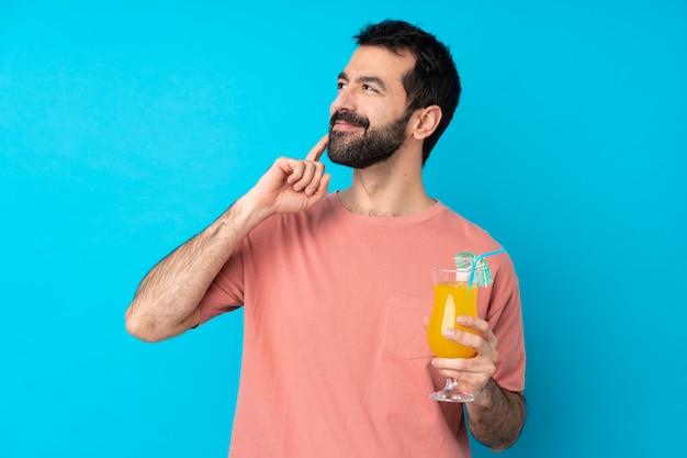 Jonge mens over het houden van een cocktail over blauw die een idee denken terwijl omhoog het kijken