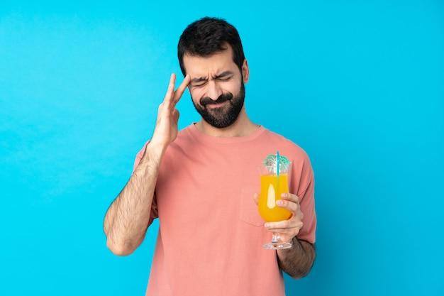 Jonge mens over het houden van een cocktail over blauw met hoofdpijn