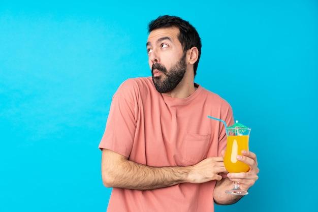 Jonge mens over het houden van een cocktail over geïsoleerd blauw