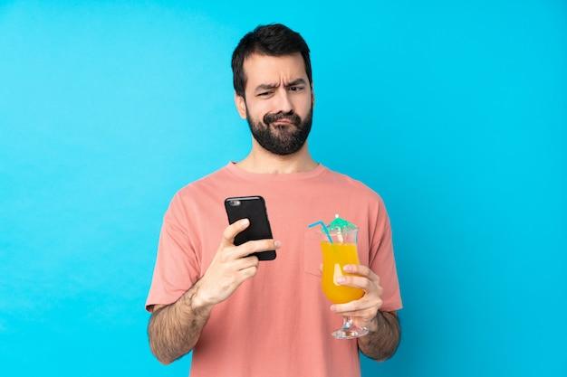 Jonge mens over het houden van een cocktail over geïsoleerde blauwe muur die en een bericht denkt verzendt