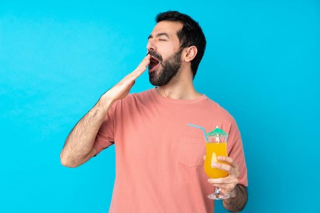 Jonge mens over het houden van een cocktail over geïsoleerde blauwe muur die en wijd open mond met hand geeuwen