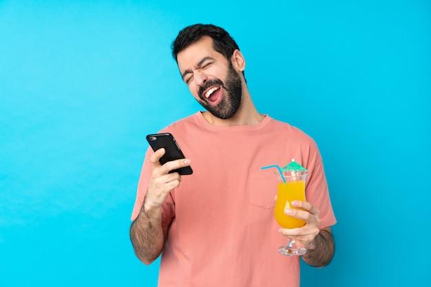 Jonge mens over het houden van een cocktail over geïsoleerde blauwe muur met telefoon in overwinningspositie