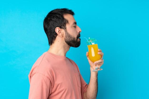 Jonge mens over het houden van een cocktail over geïsoleerde blauwe muur