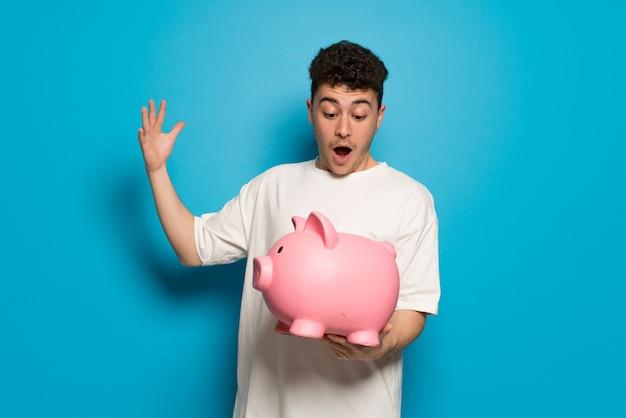 Jonge mens over op verrast blauw terwijl het houden van een spaarpot