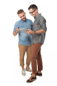 Jonge mens twee die een geïsoleerde tabletpc bekijkt