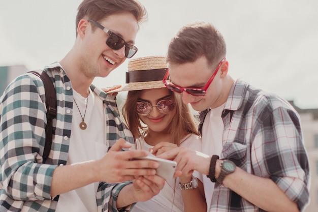 Jonge mensen bekijken foto's in mobiel en lachen